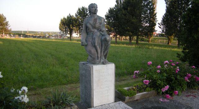 Споменик са погледом на пругу и гробље