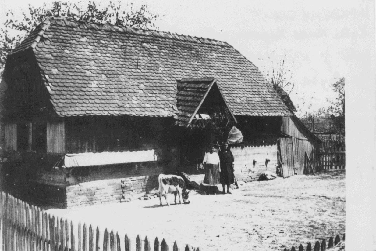 Kuća Mile Karan, ratne 1944. god. pre nego što je izgorela Pred kućom stoje Milina kćerka Ljuba i supruga Milja Snimljeno 15.06.1944. (Foto: B. Turajlić)