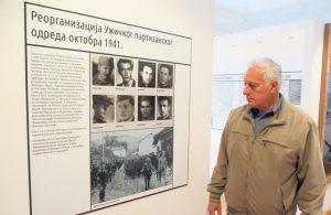Радивоје Папић испред фотографије на којој партизани и четници заједно спроводе заробљене Немце (Фото С. Јовић)