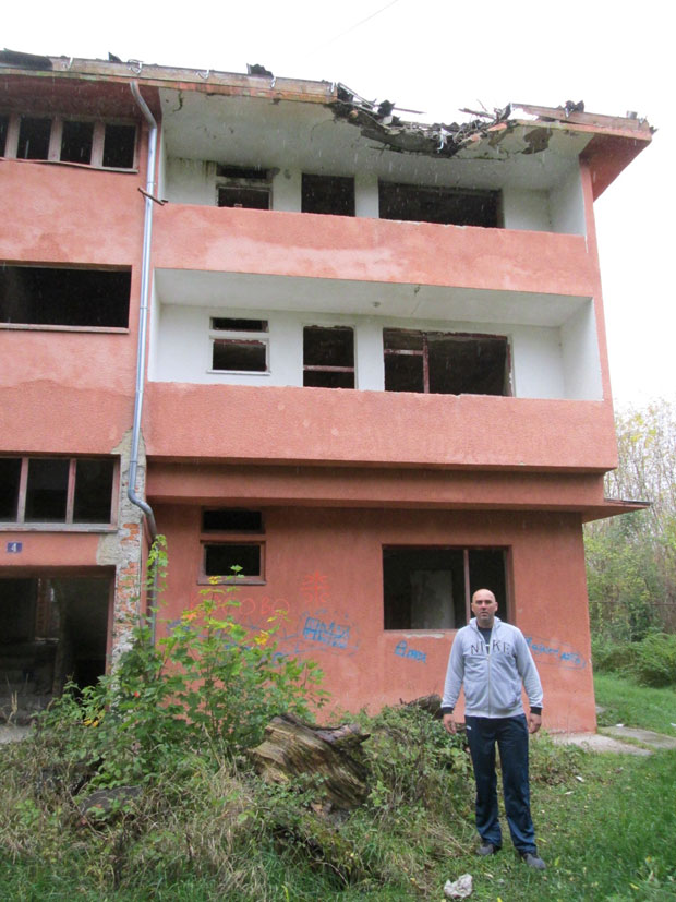 Рајко Срдић испред зграде која је оштећена у рату и још није обновљена