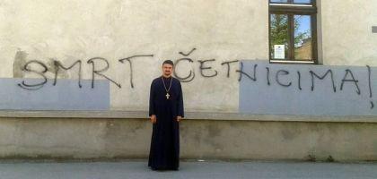 Protojerej - stavrofor Predrag Azap ispred uvredljivog grafita na parohijskom domu SPC u Vinkovcima.