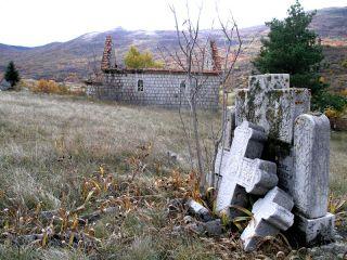 Zidina spaljene crkve i polomljeni spomenici na srpskom groblju u Donjim Rujanima