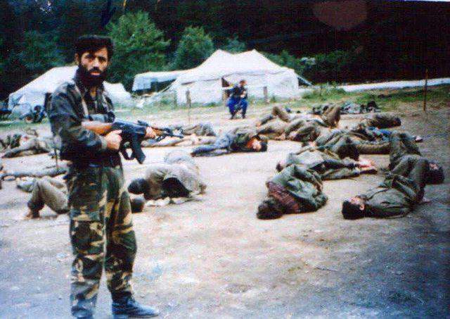 Pripadnik odreda El mudžahid pored zarobljenih srpskih vojnika