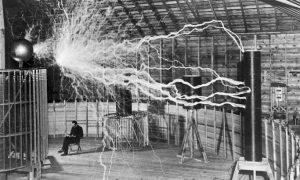"""""""Lukovi"""" strujnih udara dugi i po sedam metara: Tesla u svojoj laboratoriji u Kolorado Springsu unutar """"uveličavajućeg prenosnika"""" koji proizvodi milione volti napona wikipedia.org"""