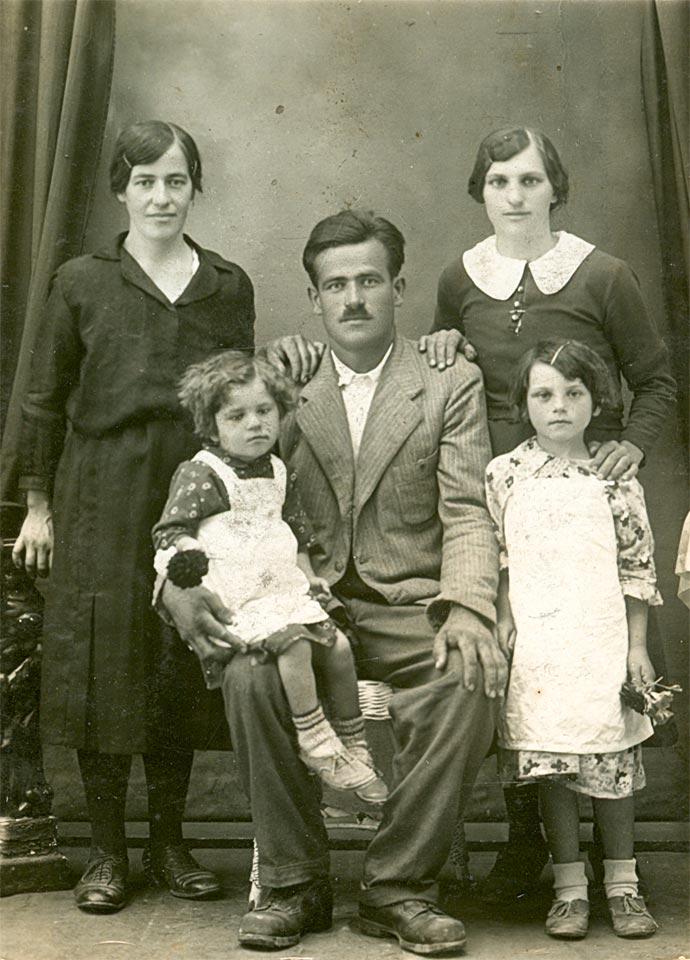 """Nikolin otac Nikola, sjedi i drži u krilu ćerku Nadu. Lijevo od njega stoji njegova starija ćerka Mileva. Iza njih stoje Nikolina tetka (tatina sestra) i njegova majka Jelena (sa """"bubi"""" kragnom). Fotografija je snimljena 1937- 1938."""