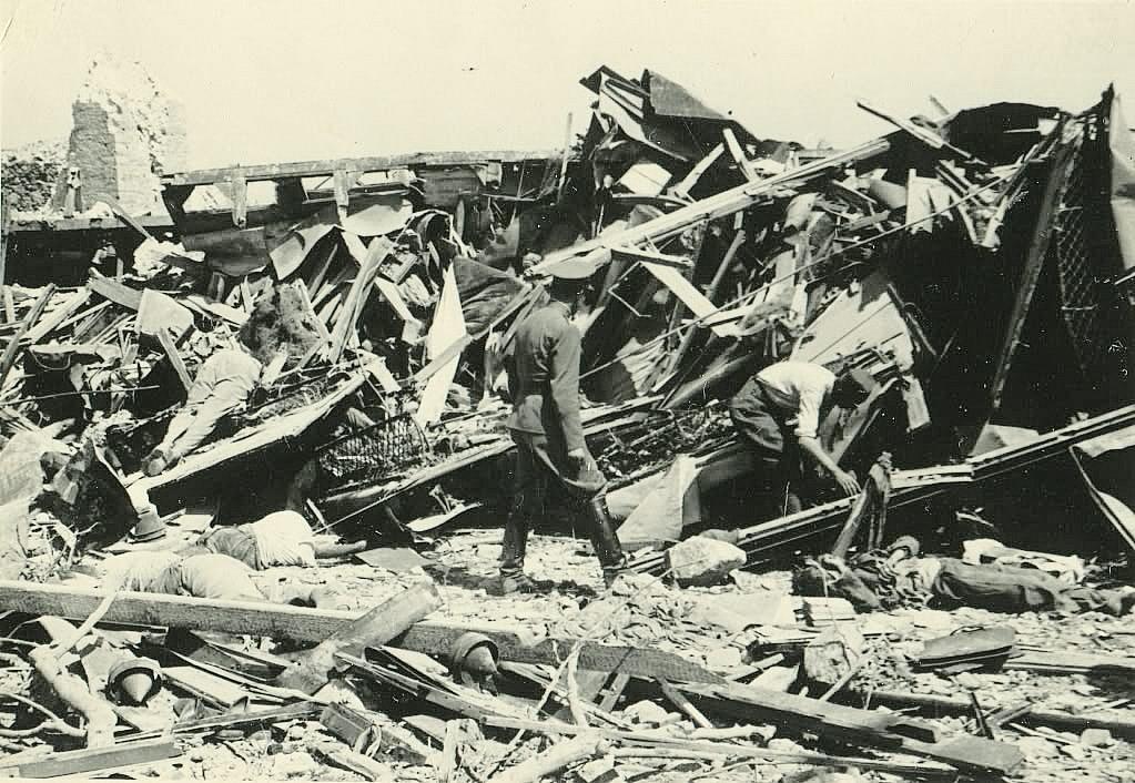Nemački oficir prebira po olupini voza u potrazi za preživelima neposredno nakon eksplozije dok se okolo vide mrtvi. Kolekcija Dušana Napijala